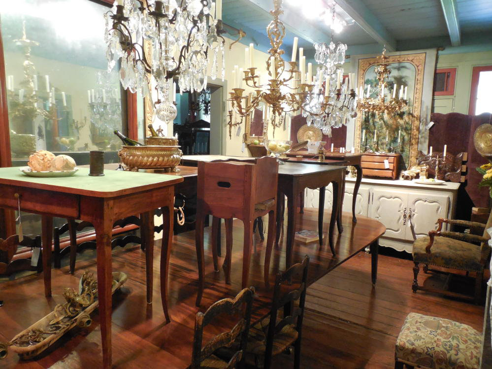 View inside Au Vieux Paris Antiques showcasing tables, lighting, seating, case pieces, mirrors and art
