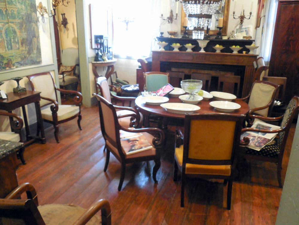 View inside Au Vieux Paris Antiques showcasing tables, porcelain, lighting, seating, and fire places