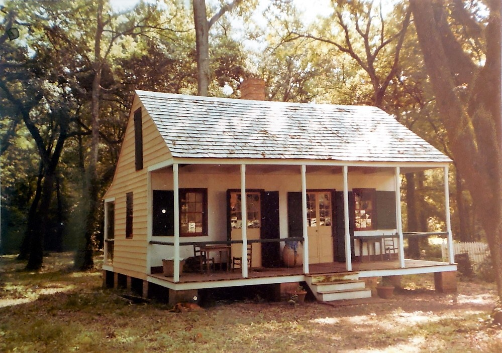 Maison de Dimanche - Acadian Sunday House - yellow siding, dark green working shutters, full length wood front porch with wood shingle gable roof. House is raised on brick piers with 3 steps, set in the woods of St. Martin Parish, Louisiana.