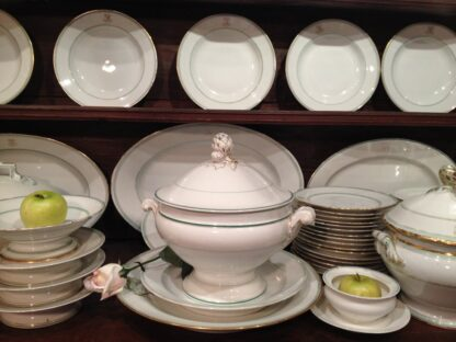 Closeup of a large Old Paris porcelain dinner set, in green and gold